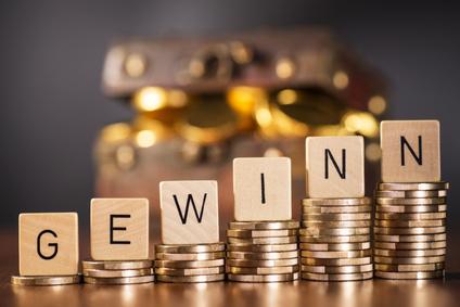 Stapel mit Münzen und dem Wort Gewinn vor einer Schatztruhe.
