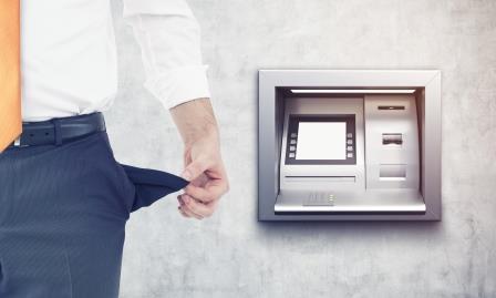 Das Bild zeigt einen Mann vor einem Geldautomaten, der kein Geld in der Tasche hat und dringend Geld leihen muss. Dazu kann er z.B. einen Sofortkredit wie den Kredit2Go nutzen.